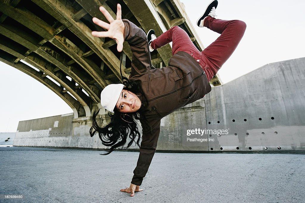 Hispanic woman break dancing under overpass