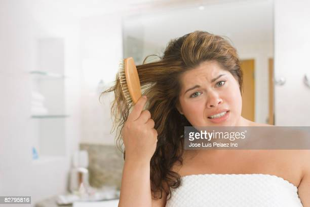 Hispanic woman brushing hair looking frustrated