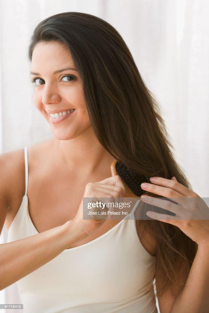 Hispanic woman brushing hair