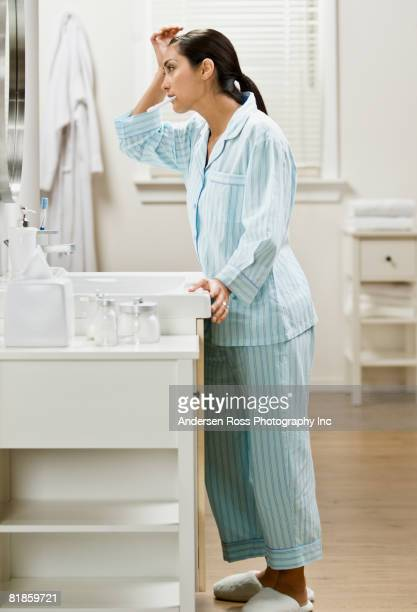 Hispanic woman brushing teeth