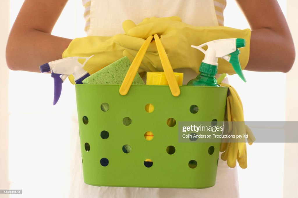 Hispanic woman carrying cleaning supplies : Stock Photo