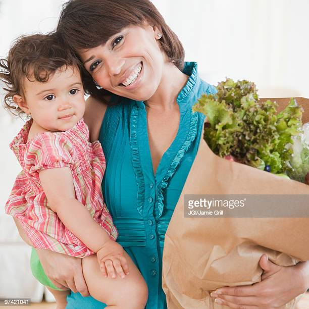 Hispanic woman carrying daughter and groceries
