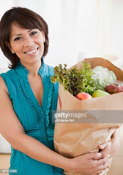 Hispanic woman carrying groceries