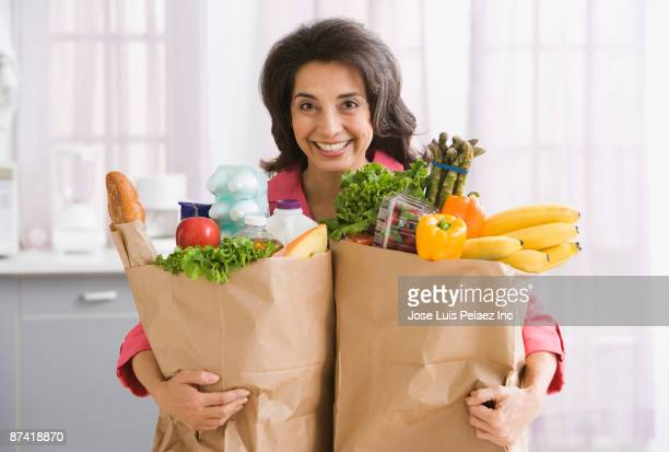 Hispanic woman carrying grocery bags