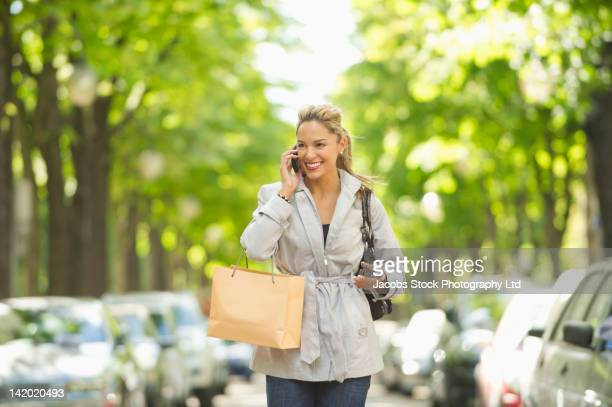 Hispanic woman carrying shopping bag and using cell phone