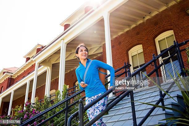 Hispanic woman carrying yoga mat on staircase