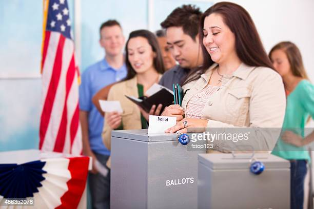 Hispanic woman casts ballot. November USA election. Voters background.