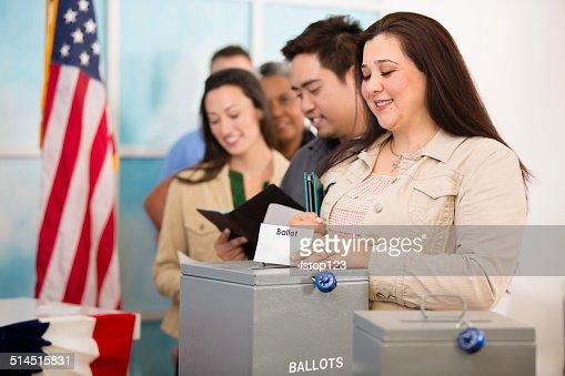 Hispanic woman casts ballot. November USA election. Voters background.