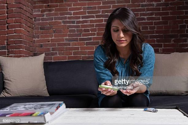Hispanic Woman Checks Her Blood Sugar