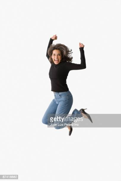Hispanic woman cheering and jumping in mid-air