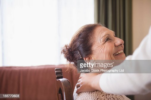 Hispanic woman comforting senior woman : Stock Photo
