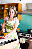 Hispanic woman cooking in kitchen with head phones