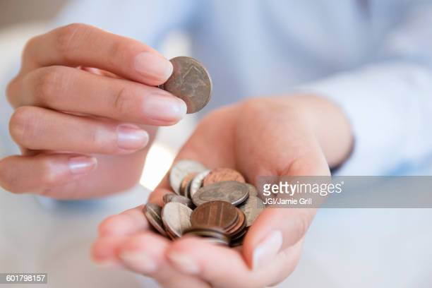 Hispanic woman counting coins
