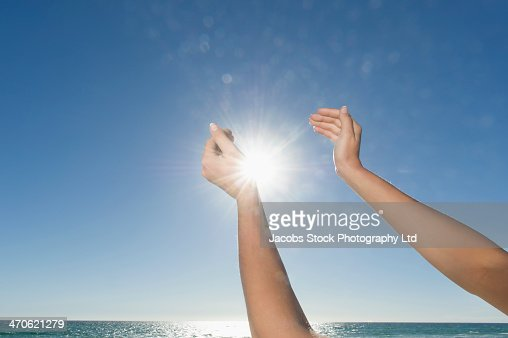 Hispanic woman cupping sun on beach