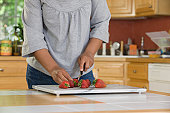 Hispanic woman cutting strawberries in the kitchen