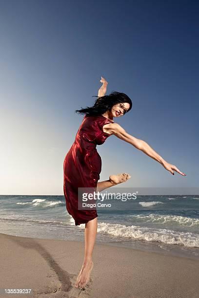 Hispanic woman dancing on beach