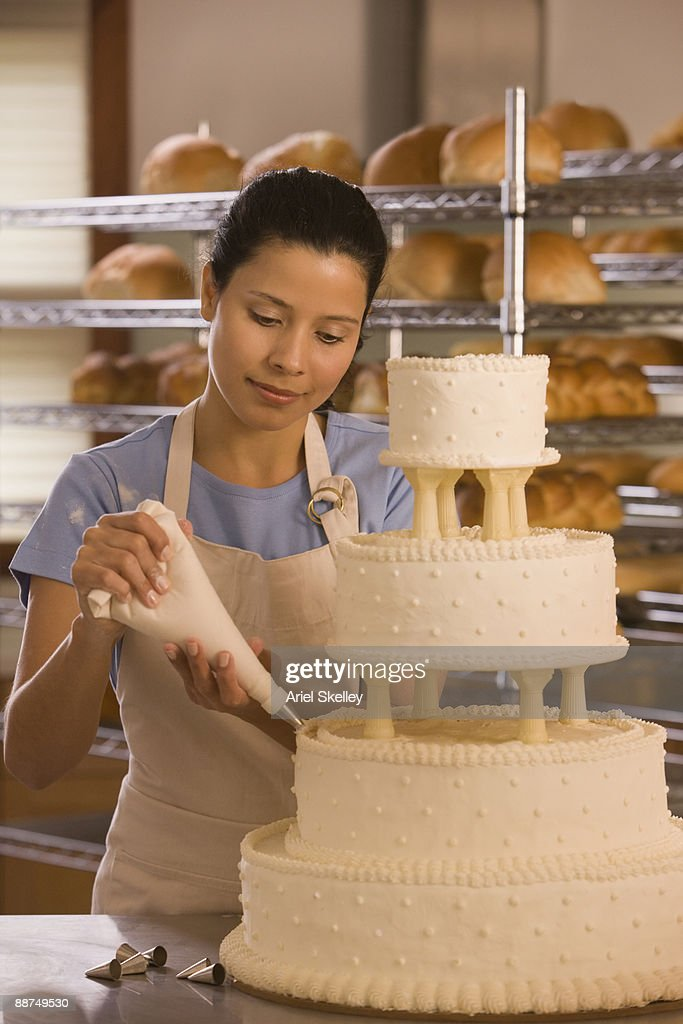 Hispanic woman decorating wedding cake
