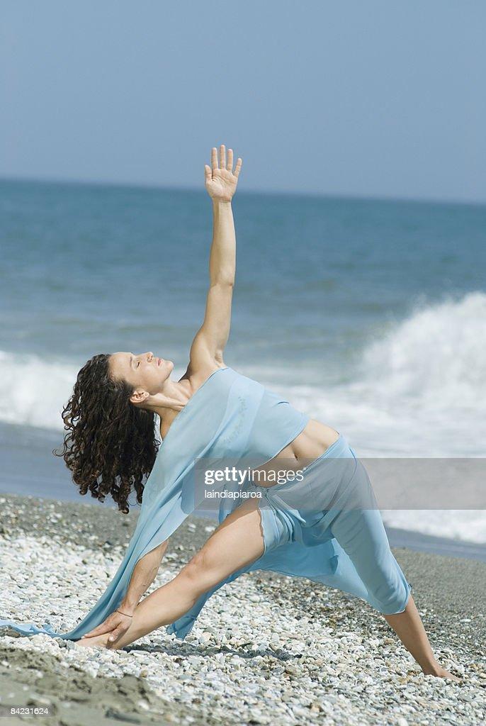 Hispanic woman doing yoga at beach : Stock Photo