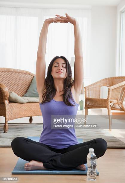 Hispanic woman doing yoga in living room