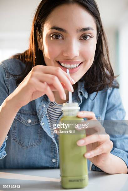 Hispanic woman drinking green juice