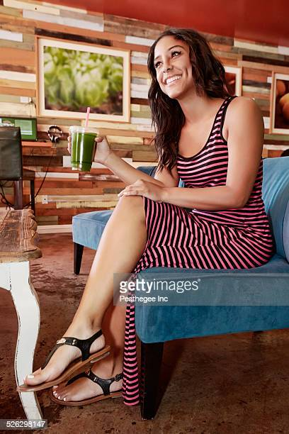 Hispanic woman drinking juice in cafe