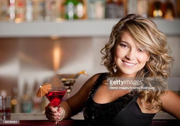 Hispanic woman drinking martini