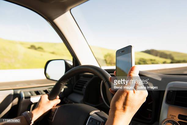 Hispanic woman driving and using cell phone