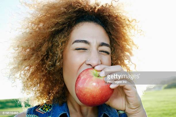 Hispanic woman eating apple outdoors