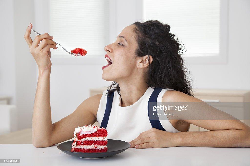 Hispanic woman eating cake in kitchen : Stock Photo