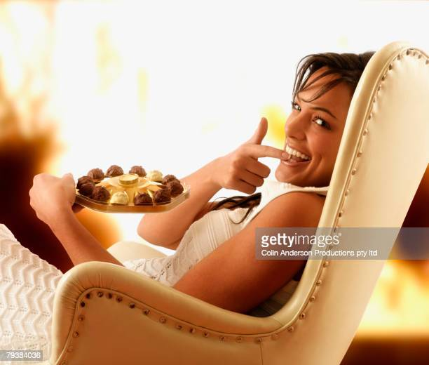 Hispanic woman eating chocolate