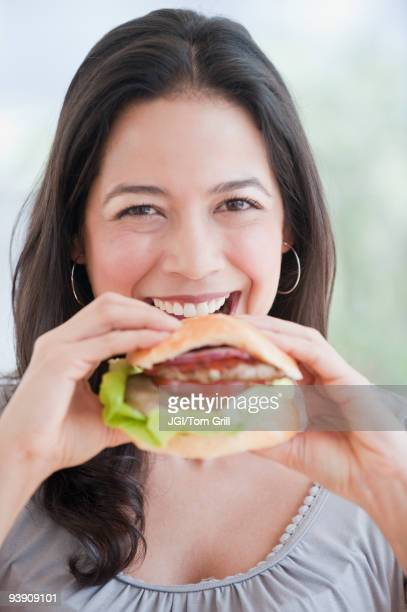 Hispanic woman eating hamburger