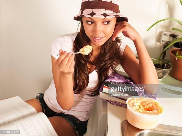 Hispanic woman eating ice cream and studying