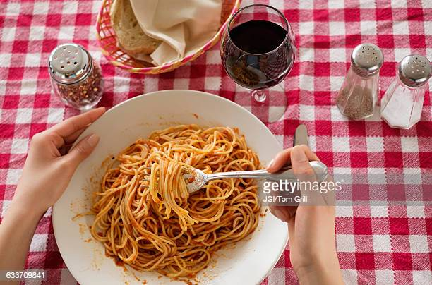 Hispanic woman eating plate of pasta