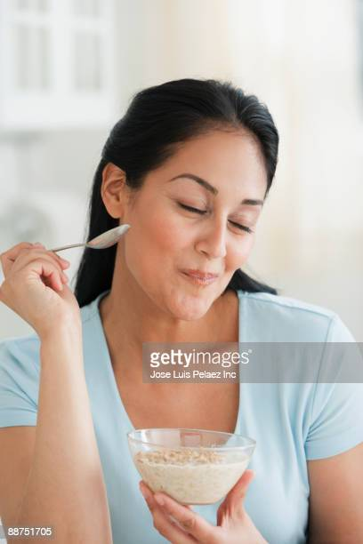 Hispanic woman enjoying bowl of cereal