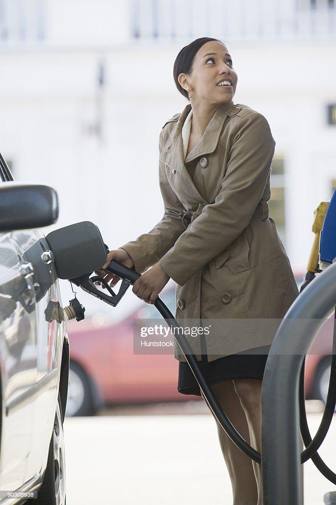 Hispanic woman filling a car at a gas station