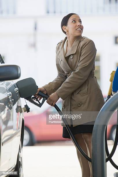 Hispanic woman filling a car at a gas station