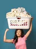 Hispanic woman flexing biceps and holding laundry basket on head