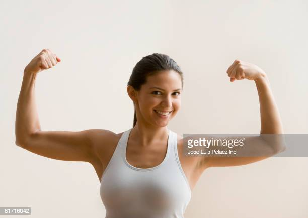 Hispanic woman flexing biceps muscles