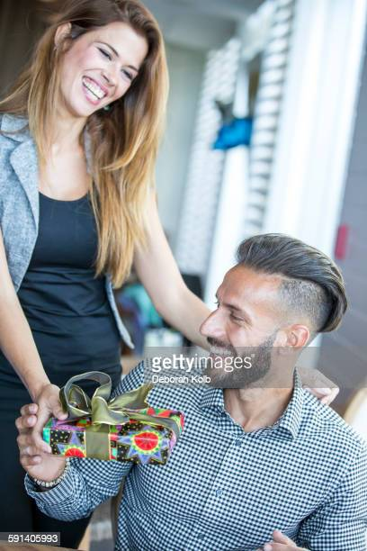 Hispanic woman giving boyfriend gift