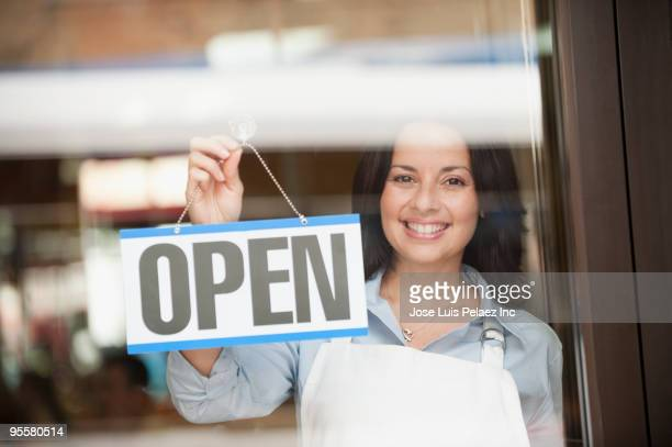 Hispanic woman hanging open sign on door