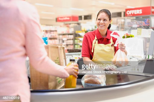 Hispanic woman helping customer at grocery checkout