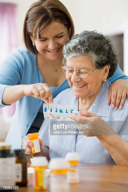 Hispanic woman helping mother with medication