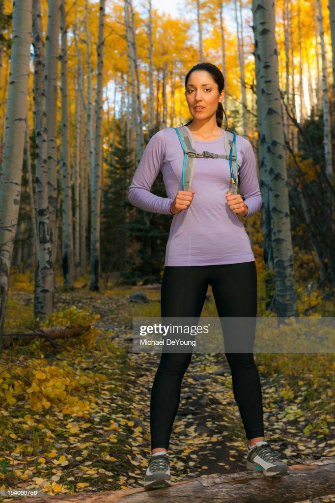 Hispanic woman hiking in woods : Stock Photo