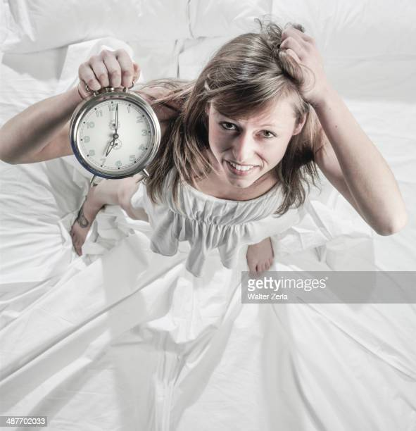 Hispanic woman holding alarm clock in bed