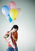 Hispanic woman holding balloons and flowers