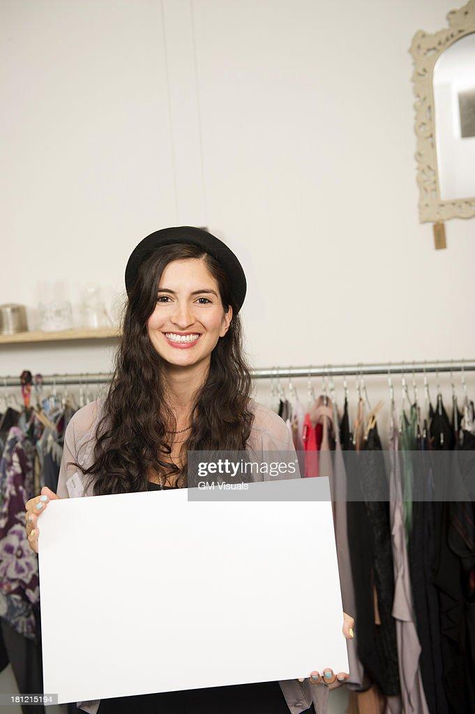 Hispanic woman holding blank card in shop : Stock Photo