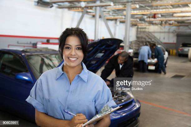 Hispanic woman holding clipboard in auto body shop