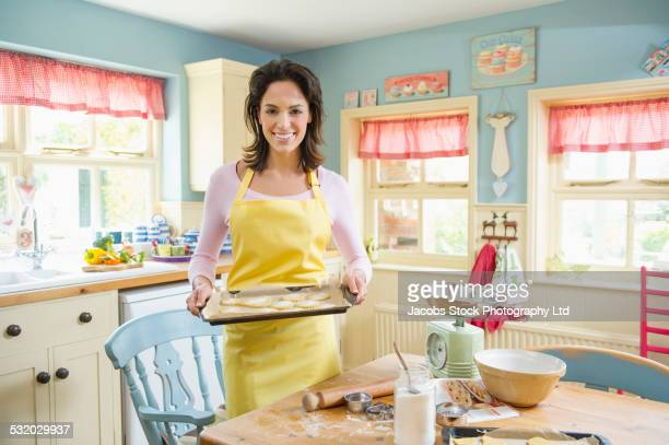 Hispanic woman holding cookie sheet in kitchen