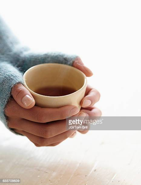 Hispanic woman holding cup of tea