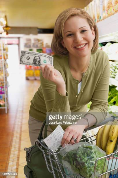 Hispanic woman holding dollar bill in grocery store